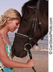 Girl with a horse by the sea