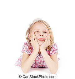 Funny little girl lying on her stomach on the floor with her...