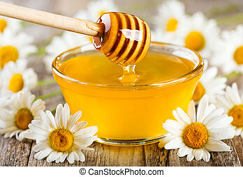 pouring honey from wooden stick into bowl