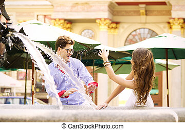 Happy couple playing in the fountain