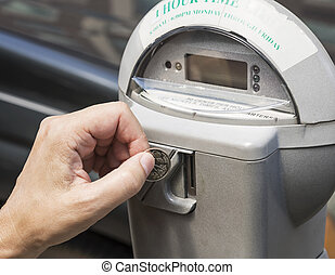 parking meter - A hand putting a coin in a parking meter
