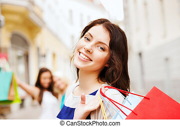 girls with shopping bags in city