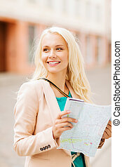 girl looking into tourist map in the city - holidays and...