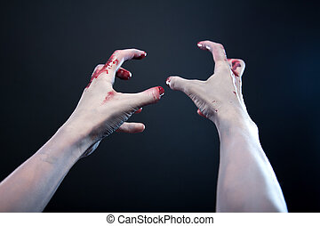 Grey skin bloody zombie hands, studio shot over gray...