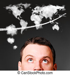 man is looking up at world map shaped clouds