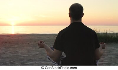 Young Man Meditating by the Sea - Handsome man sitting in...