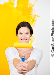Smiling woman with a paint roller holding it out at arms...