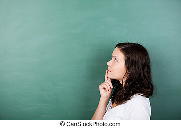 Student standing solving a problem - Attractive young female...