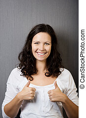 Woman Gesturing Thumbs Up Against Wall - Portrait of...