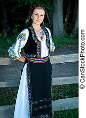 Portrait of young beautiful woman posing outside in Romanian...