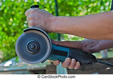 Angle Grinder - Switched on angle grinder in the man hands....