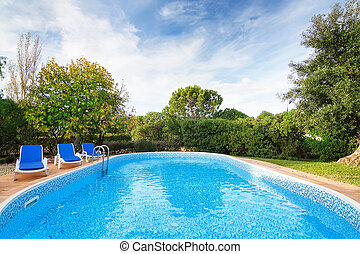 Luxury summer swimming pool with sun loungers. For relaxation and swimming. Summer.