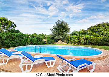 Luxury swimming pool with sun loungers. For relaxation and swimming. Summer.