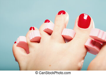 foot pedicure applying red toenails on blue - foot pedicure...
