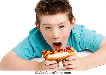 Hungry young boy eating a hotdog - Young boy with spikey...