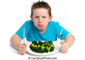 Grumpy young boy not happy about eating broccoli - A young...