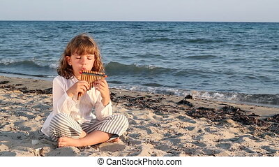 little girl play pan pipe on beach