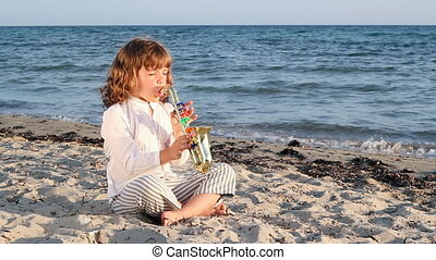 little girl play saxophone on beach
