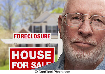Depressed Senior Man in Front of Foreclosure Sign and House...