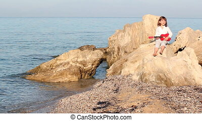 little girl sitting on a rock