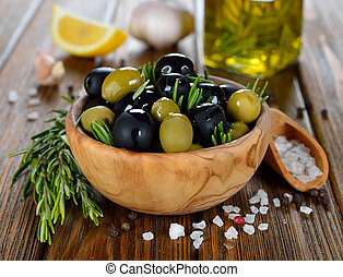 Olives with rosemary in a wooden bowl on a brown table