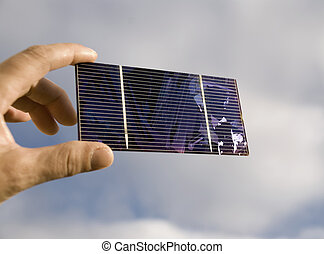 solar cell in a hand against a cloudy sky