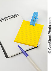 yellow post note, empty white note, pen and blue clip with...