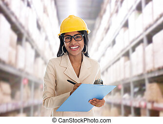 Indian woman in warehouse - Smiling Indian woman doing stock...