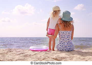 Mama and her little daughter on the beach - Mama and her...
