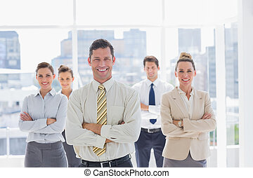 Smiling handsome businessman with his team in a modern...