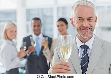 Businessman smiling at camera with champagne with team...
