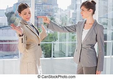 Angry businesswoman pointing at her rival