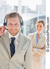 Smiling call centre agent with colleague behind him