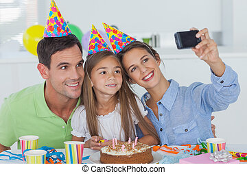 Woman taking pictures of her family during a birthday party...