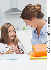 Mother chatting with her daughter drawing in the kitchen