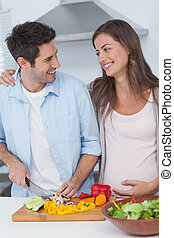 Pregnant woman looking at husband chopping vegetables for a...