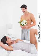 Handsome man offering flowers to his girlfriend in bed