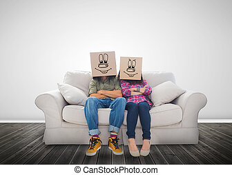 Couple wearing funny boxes on their head on a couch