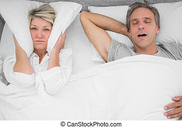 Man snoring loudly as partner blocks her ears at home in...