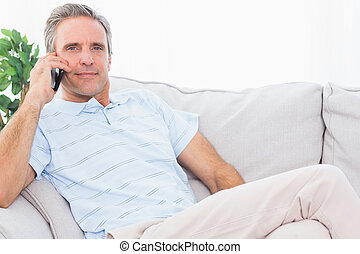 Man on his couch making phone call and smiling at camera