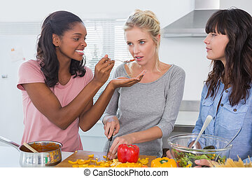 Cheerful friends preparing a meal together at home in...