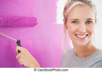 Smiling woman painting her wall in pink and looking at...