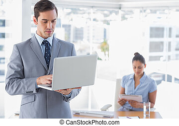Businessman using laptop standing in office