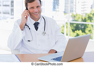 Happy doctor phoning in his office - Happy doctor phoning in...
