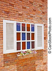White window with flower pots on the brick wall.