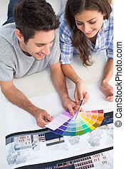 Couple looking at a color chart to decorate their house -...