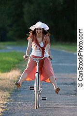 Retro girl on old bike - Woman in orange skirt and white hat...