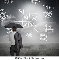 Businessman looking at noughts and crosses and holding...