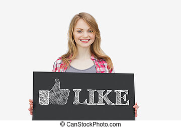 Smiling girl holding panel with thumb up representing social network logo on white background