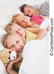 Young girl awake next to her sleeping family in bed